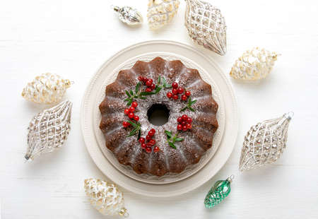 Christmas bundt cake served on white wooden table and decorated with Xmas holiday decorations, top down view