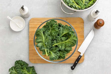Fresh kale leaves in a bowl standing on a kitchen table ready for cooking, healthy or clean eating concept, overhead view image