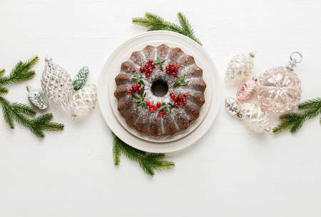Christmas bundt cake served on white wooden table and decorated with Xmas holiday decorations, top down view, blank space for a greeting text