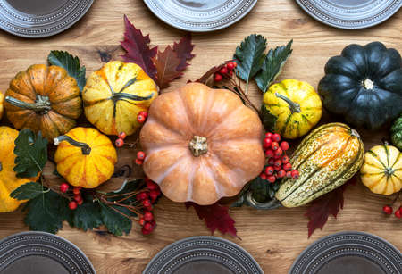 Thanksgiving country style table setting natural decoration idea, overhead view on wooden table decorated with pumpkins and autumn natural decor