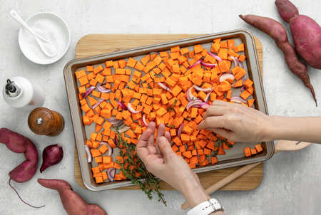 Sweet potato diced and put in a sheet pan with red onion and thyme, view from above on womans hands spearing thyme twigs around the ingredients