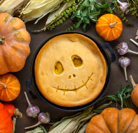 Halloween kids party pumpkin pie with a cute smiling face, top view