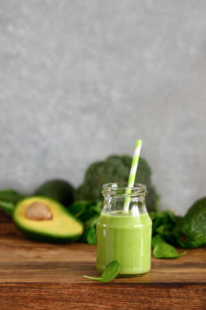 Green detox smoothies made of spinach and avocado in a glass bottle with a straw, front view 写真素材