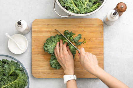 Fresh kale leaves are cut by womans hands on a cutting board, healthy or clean eating concept, overhead view image 写真素材