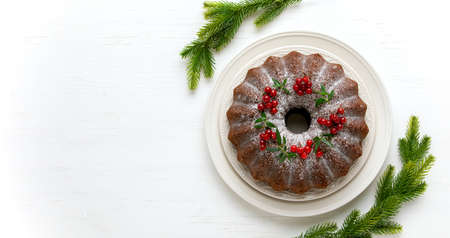 Christmas bundt cake served on white wooden table and decorated with fresh cranberries, Christmas baking concept or idea, composition with blank space for a greeting text 写真素材