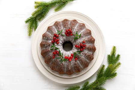 Christmas bundt cake served on white wooden table and decorated with fresh cranberries, Christmas baking concept or idea, overhead view