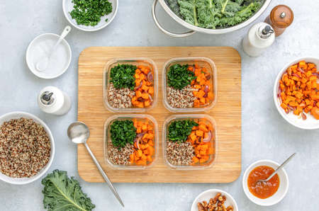 Quinoa, kale and roasted sweet potato lunch boxes are standing on a kitchen table with ingredients for cooking, overhead view, fall healthy take-away lunch recipe concept 写真素材