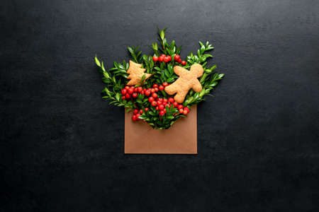 Christmas greeting card minimalist concept, open envelope with holiday natural botany decorations,  evergreen branches and red berries, and ginger bread man and fir tree, top down view, blank space fo