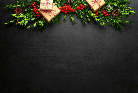 Noel or Christmas dark background with gift boxes and natural winter holidays traditional botany decor such as red berries and evergreen branches arranged in a header, flat lay composition with copy space for a greeting text