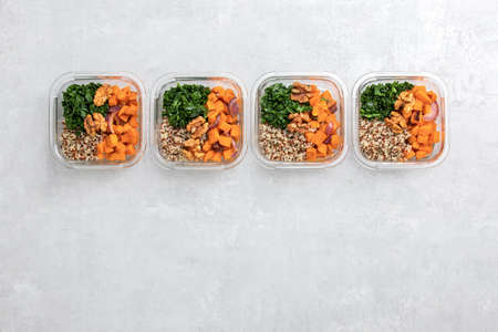 Sauteed kale, quinoa and roasted sweet potato lunch box bowl, view from above, blank space for a text