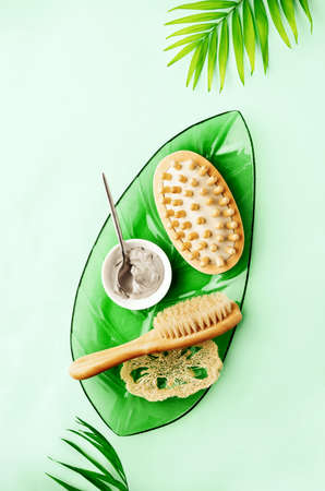 Spa setting background with ready to use cosmetic clay and massage brushes, top down view