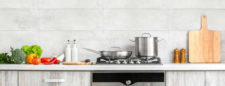 Fresh clean vegetables being put on a kitchen desk top, ready for cooking, front view of modern kitchen countertop with domestic culinary utensils on it, home healthy cooking concept banner