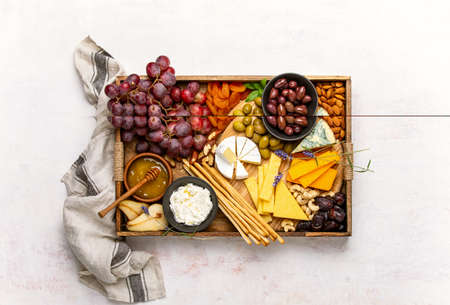 Cheeseboard overhead view, cheese assortment served with honey, grapes nuts and olives, healthy food concept Banque d'images
