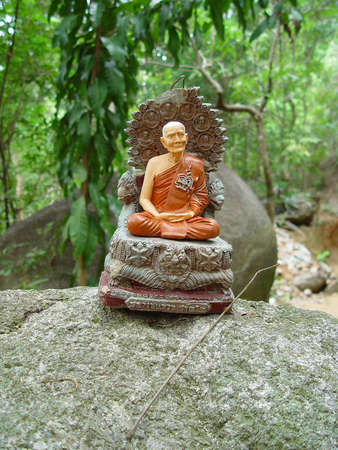 little statue of buddaha in the jungle photo
