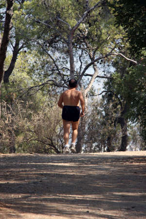 man is jogging in forest half  photo