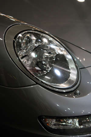 sports car front light detail from exhibition vertical