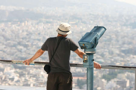 man tourist watching the view of athens from the top of lycabetus Foto de archivo
