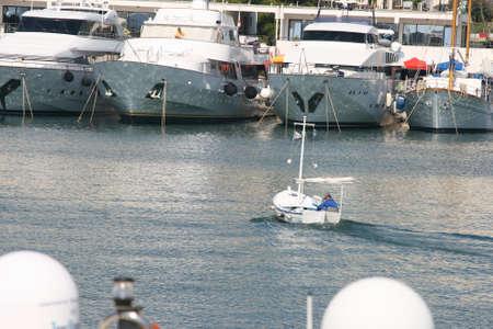sailling: small boat sailling to marina between yachts
