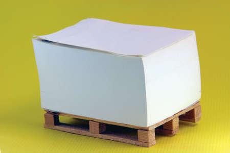wooden paper palete miniature in yellow background Banco de Imagens
