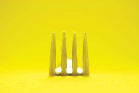 creative concept gourmet fork detail in yellow background
