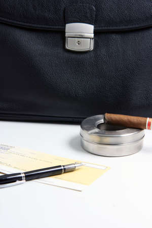 prespective: focus on cigar financial deal check writing cigar with black leather briefcase background praspective business concepts