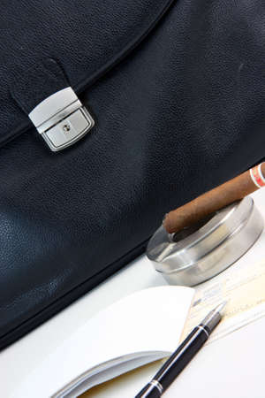 prespective: financial deal check writing cigar with black leather briefcase background praspective business concepts Stock Photo