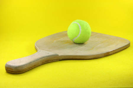 prespective: beach wooden racket with yellow ball in yellow background prespective Stock Photo