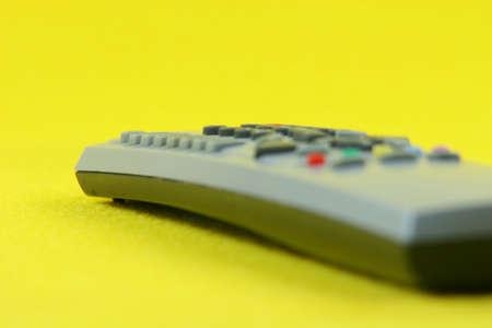 prespective: detail from television remote control in yellow background technology concepts Stock Photo