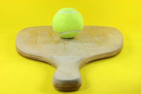 prespective: beach wooden racket with yellow ball in yellow background