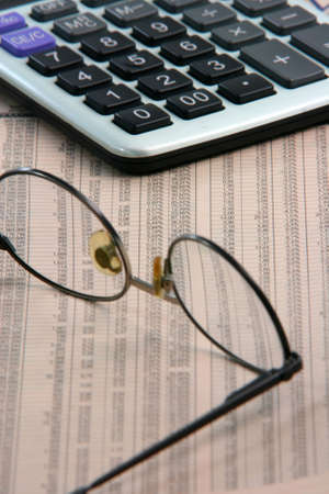 business and finance concepts spectacles close up on financial newspaper with stock prices and calculator Foto de archivo