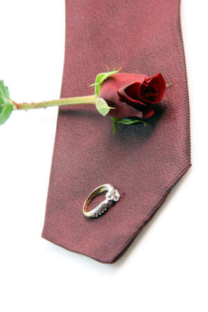 wedding proposal equipment diomond ring, red silk tie and red rose on white background vertical photo
