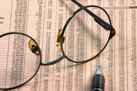 reviewing: business and finance concepts spectacles close up on financial newspaper with stock prices and ballpen