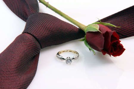 wedding proposal equipment diomond ring, red silk tie and red rose on white background vertical