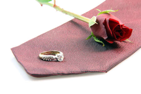 wedding proposal equipment diomond ring, red silk tie and red rose on white background photo