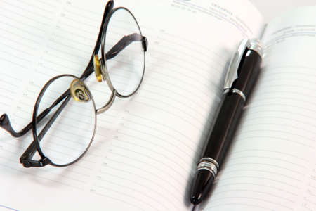 ball pen: spectacles with black ball pen on open diary business concepts Stock Photo