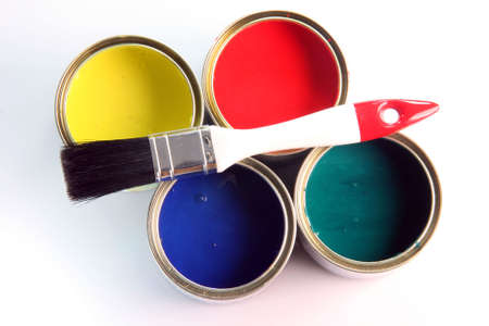 white small paint brush on four open paint cans on white background Foto de archivo