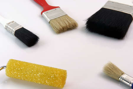 detail from four paint brushes and paint roll on white background hardware tools with copy space photo
