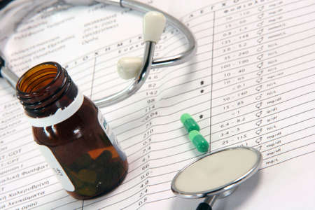 stethoscope sheet of medical lab test results and bottle of medicine capsules
