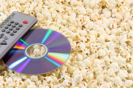 television remote control and dvd disc movie on pop corn background food and entertainment conceps
