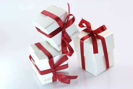 three white gift boxes with red ribbon for valentines day and love gifts photo