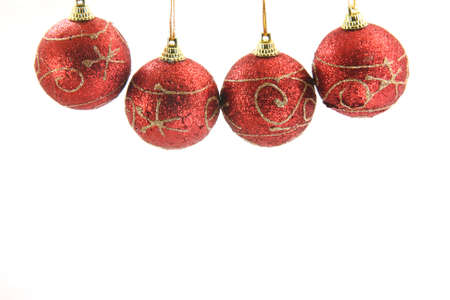 selebration: four red christmas decoration balls hanging isolated on white background front view