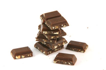 pile of chocolate pieces closeup with copy space isolated on white background food and sweets concepts photo