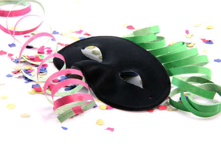 carnival concepts paper confetti streamers and black mask isolated on white background
