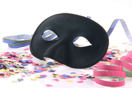 carnival concepts paper closeup black mask with confetti and streamers isolated on white background