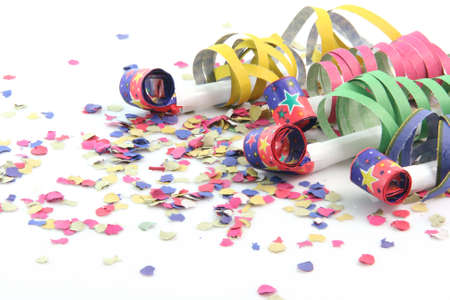 party concepts  paper confetti with streamers and four party blowers on white background Foto de archivo
