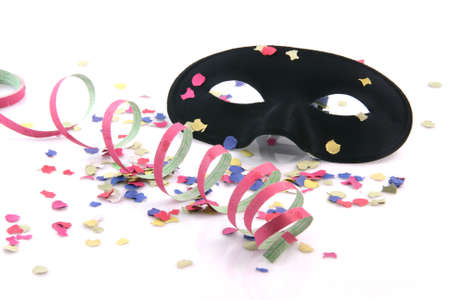 carnival concepts paper confetti streamers and black mask isolated on white background photo