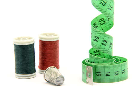 sewing items measure tape cotton strings and thimble isolated on white background
