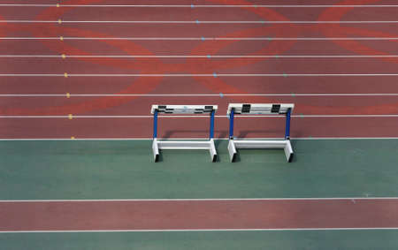 detail from empty athletics race track and stack of hurdles  photo