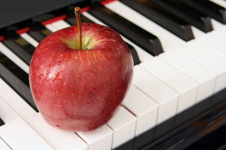 red apple closeup on piano keyboard music education and healthy food