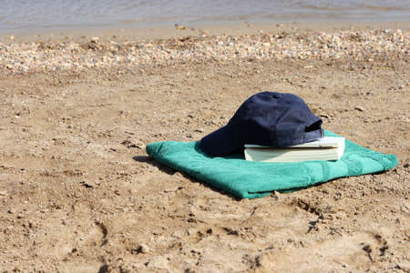 blue baseball hat on green towel by the see and book Stock Photo - 4078191